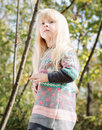 Pretty little blond girl at the forest close up with long hair wearing autumn fashion outfit woodland with tall trees background Royalty Free Stock Photos