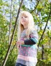 Pretty little blond girl at the forest close up with long hair wearing autumn fashion outfit woodland with tall trees background Stock Photos