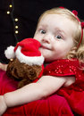 Pretty little blonde girl with red clothes and toy a toddler dressed in looking at the camera she has a her christmas theme Stock Image