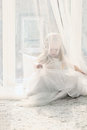 Pretty little blonde girl sits near big window and hides Royalty Free Stock Photo