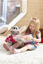 Pretty little blonde girl sits near soft toy on carpet in cozy room and reads book Royalty Free Stock Photography