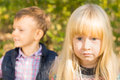 Pretty little blue eyed blond girl staring intently at the camera with a young boy looking to the side in the background Royalty Free Stock Image