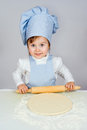 Pretty little girl chief cooking pizza over gray background Royalty Free Stock Image