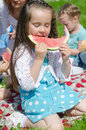 Pretty little girl eating watermelon in the park Stock Image