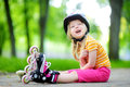 Pretty little girl learning to roller skate on beautiful summer day in a park Royalty Free Stock Photo