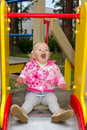 Pretty little girl play on playground in the park. Royalty Free Stock Images