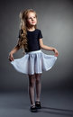 Pretty little girl posing straightened her skirt on gray background Royalty Free Stock Photography