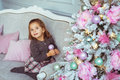 Pretty little girl sits on a sofa near Christmas tree and looks up
