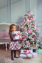 Pretty little girl stands with a gift box at hands near Christmas tree and looks to side