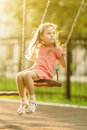 Pretty little girl swinging on seesaw beneath bright shining in summertime Stock Images