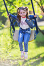 Pretty little girl swinging on seesaw in summertime Stock Images