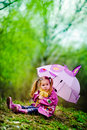 Pretty little girl with umbrella in the park Stock Photo