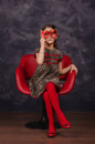 Pretty little girl wearing beautiful dress sitting in red armchair. She is wearing red masquerade carnival mask. Studio shot. Royalty Free Stock Photo