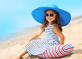 Pretty little smiling girl in a striped dress and straw hat relaxing resting on the beach near sea summer vacation travel concept Stock Photography