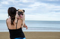Pretty lonely asia girl hold a cute dog puppy pug against beach and sky background Royalty Free Stock Photo