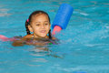 Pretty mixed race child swimming in pool during summer Royalty Free Stock Photography