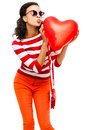 Pretty mixed race girl holding red heart balloon a Stock Photos