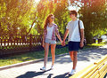 Pretty modern young couple in love walking in sunny summer day