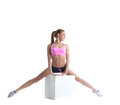Pretty muscular athlete doing split on cube in studio Stock Photography