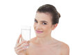 Pretty natural brown haired model holding a glass of water on white background Royalty Free Stock Image