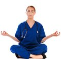 Pretty nurse doing meditation isolated on white Stock Photos