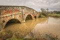 Pretty old brick bridge over flooded river Royalty Free Stock Photo