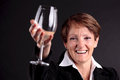 Pretty old woman rising up a glass of wine (focus on face) Royalty Free Stock Photo