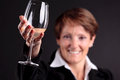 Pretty old woman rising up a glass of wine (focus on hand) Royalty Free Stock Photo