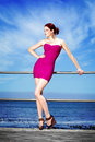 Pretty in pink fashion model posing at the beach front Royalty Free Stock Photo