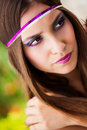 Pretty in plum beautiful brunette model wearing a purple and gold sequined headband resting her hand on her shoulder looking away Stock Photos