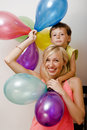Pretty real family with color balloons on white background, blond woman with little boy at birthday party bright smiling Royalty Free Stock Photo