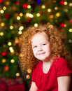 Pretty red haired little girl wearing red dress sitting in front of christmas tree with colorful lights Royalty Free Stock Photography