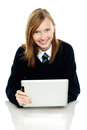 Pretty schoolgirl holding newly launched tablet pc Royalty Free Stock Photos