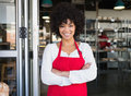 Pretty server in red apron with arms crossed Royalty Free Stock Photo