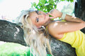Pretty sexy blonde woman lying on tree bench Royalty Free Stock Photo