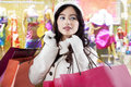 Pretty shopaholic carrying christmas shopping bags attractive teenage girl wearing winter coat and some of in the center Royalty Free Stock Photography