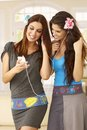 Pretty sisters listening to music on mp3 player Royalty Free Stock Photo