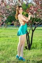 Pretty slim leggy woman wearing turquoise dress and shoes touching leaves of the tree Royalty Free Stock Photo