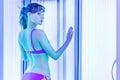 Pretty slim woman getting sun tan in solarium Royalty Free Stock Photo