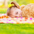 Pretty small girl lying down on green field playing game with big brown teddy bear cute child enjoying spring nature Stock Image