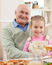 Pretty small girl is visiting her grandfather cheerful old men dining with his granddaughter they are sitting and embracing the Royalty Free Stock Images