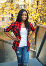 Pretty smiling african woman wearing a red checkered shirt in city Royalty Free Stock Photos