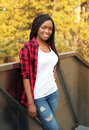 Pretty smiling african woman wearing red checkered shirt in city Royalty Free Stock Photo