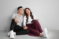 Pretty smiling asian couple in love together sitting on floor en Royalty Free Stock Photo