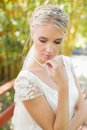Pretty smiling blonde bride standing on a bridge looking down in the countryside Stock Photo