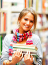 Pretty smiling lady holding books in library Stock Images