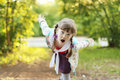 Pretty smiling little girl with braids depicts bird at sunny day shallow dof Stock Images