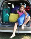 Pretty little girl fills the suitcases on the car Royalty Free Stock Photo