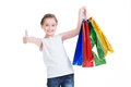 Pretty smiling little girl with shopping bags keeps thumb up isolated on white Stock Images