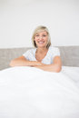 Pretty smiling mature woman sitting on bed portrait of a at home Stock Photography